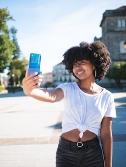 Jonge zwarte vrouw die een foto selfie op straat, het dragen van vrijetijdskleding
