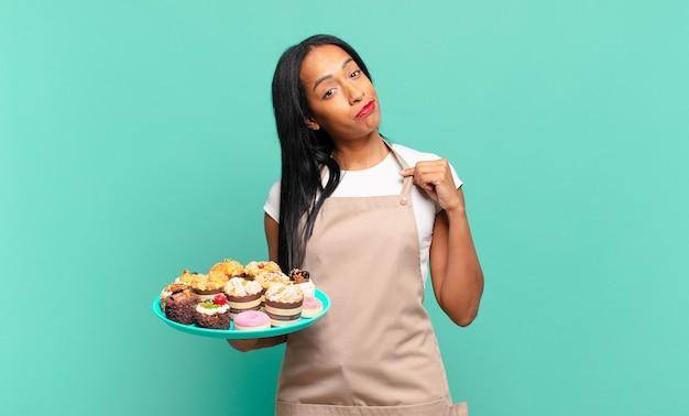 Jonge zwarte vrouw die er arrogant, succesvol, positief en trots uitziet, wijzend naar zichzelf. bakkerij chef-kok concept