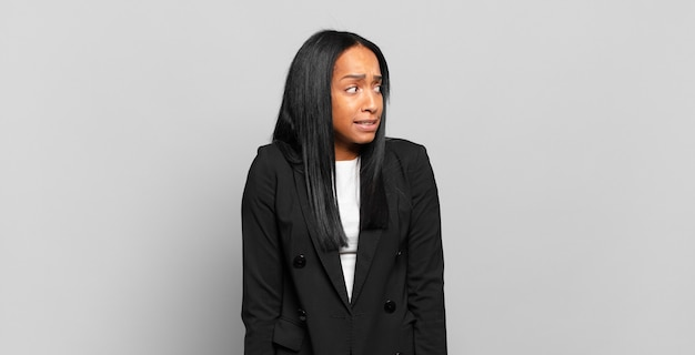 Jonge zwarte vrouw die er bezorgd, gestrest, angstig en bang uitziet, in paniek raakt en tanden op elkaar klemt. bedrijfsconcept
