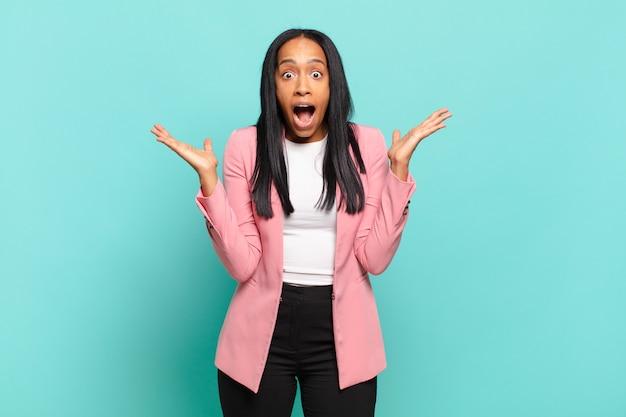 Jonge zwarte vrouw die er blij en opgewonden uitziet, geschokt door een onverwachte verrassing met beide handen open naast het gezicht