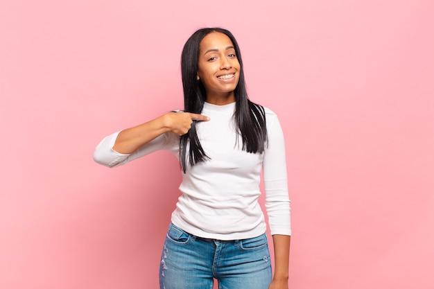 Jonge zwarte vrouw die er blij, trots en verrast uitziet, vrolijk naar zichzelf wijst, zich zelfverzekerd en verheven voelt