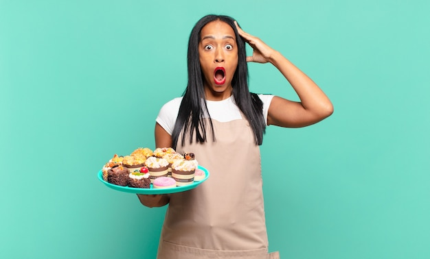 Jonge zwarte vrouw die er blij, verbaasd en verrast uitzag, lachte en zich verbluffend en ongelooflijk goed nieuws realiseerde. bakkerij chef-kok concept