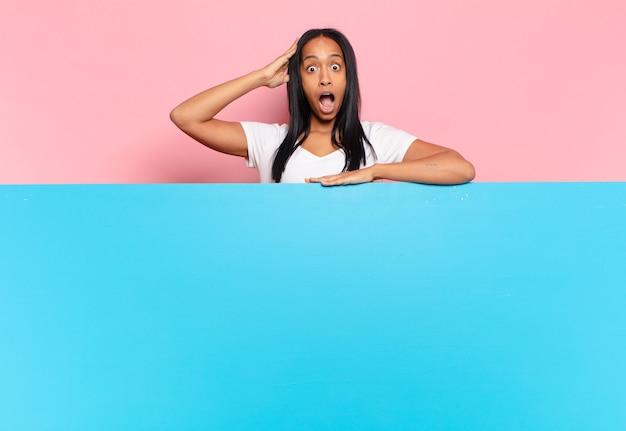 Jonge zwarte vrouw die er blij, verbaasd en verrast uitziet