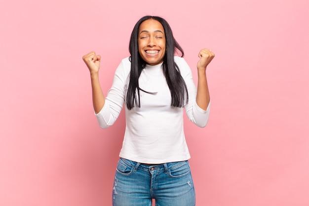 Jonge zwarte vrouw die er buitengewoon blij en verrast uitziet en succes viert
