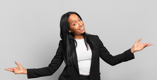 Jonge zwarte vrouw die er gelukkig, arrogant, trots en zelfvoldaan uitziet
