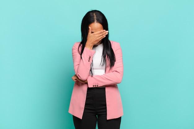 Jonge zwarte vrouw die er gestrest, beschaamd of overstuur uitziet, met hoofdpijn, gezicht bedekt met de hand. bedrijfsconcept