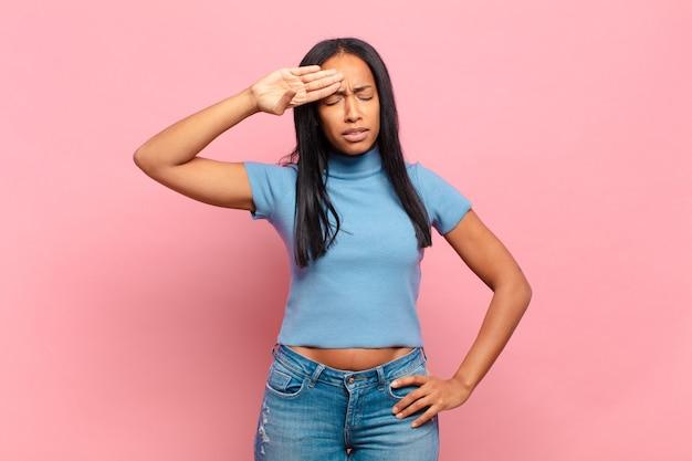 Jonge zwarte vrouw die er gestrest, moe en gefrustreerd uitziet en het zweet van het voorhoofd droogt