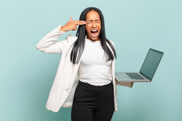 Jonge zwarte vrouw die er ongelukkig en gestrest uitziet, zelfmoordgebaar maakt een pistoolteken met de hand, wijzend naar het hoofd. laptopconcept