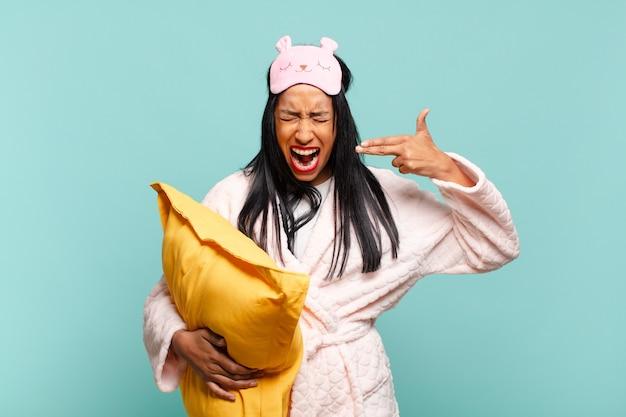 Jonge zwarte vrouw die er ongelukkig en gestrest uitziet, zelfmoordgebaar maakt een pistoolteken met de hand, wijzend naar het hoofd. pyjama concept