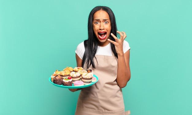 Jonge zwarte vrouw die er wanhopig en gefrustreerd, gestrest, ongelukkig en geïrriteerd uitziet, schreeuwend en schreeuwend. bakkerij chef-kok concept