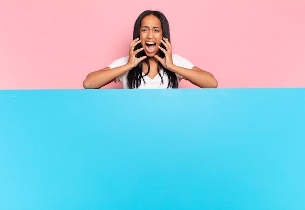 Jonge zwarte vrouw die er wanhopig en gefrustreerd, gestrest, ongelukkig en geïrriteerd uitziet, schreeuwend en schreeuwend. kopieer ruimteconcept