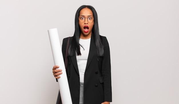 Jonge zwarte vrouw die erg geschokt of verrast kijkt, starend met open mond en zegt wow. architect concept