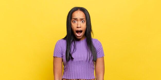 Jonge zwarte vrouw die erg geschokt of verrast kijkt, starend met open mond en zegt wow