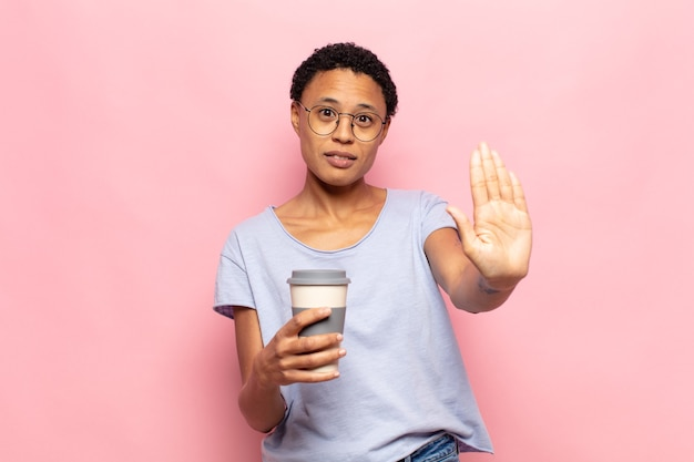 Jonge zwarte vrouw die ernstig, streng, ontevreden en boos kijkt die open palm toont die stopgebaar maakt