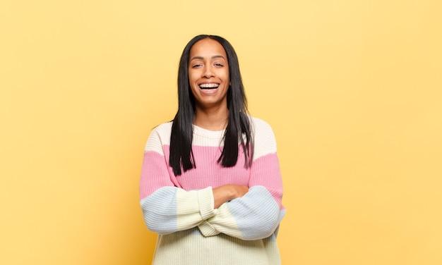 Jonge zwarte vrouw die eruit ziet als een gelukkige, trotse en tevreden uitvoerder die met gekruiste wapens glimlacht