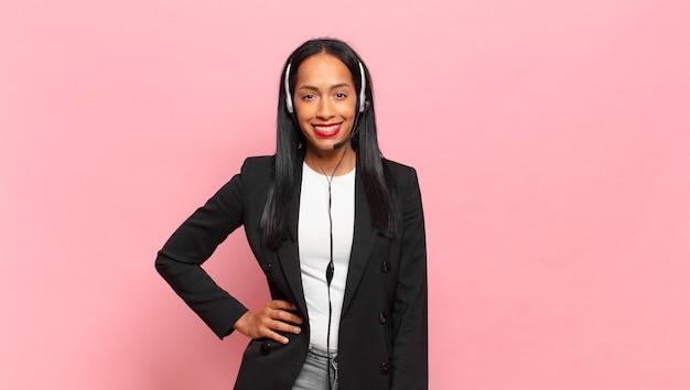 Jonge zwarte vrouw die gelukkig lacht met een hand op de heup en zelfverzekerde, positieve, trotse en vriendelijke houding. telemarketing concept