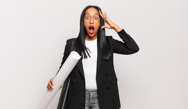 Jonge zwarte vrouw die gelukkig, verbaasd en verrast kijkt, glimlacht en verbazingwekkend en ongelooflijk goed nieuws realiseert. architect concept