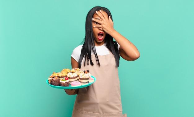 Jonge zwarte vrouw die geschokt, bang of doodsbang kijkt, haar gezicht bedekt met de hand en tussen de vingers gluurt. bakkerij chef-kok concept