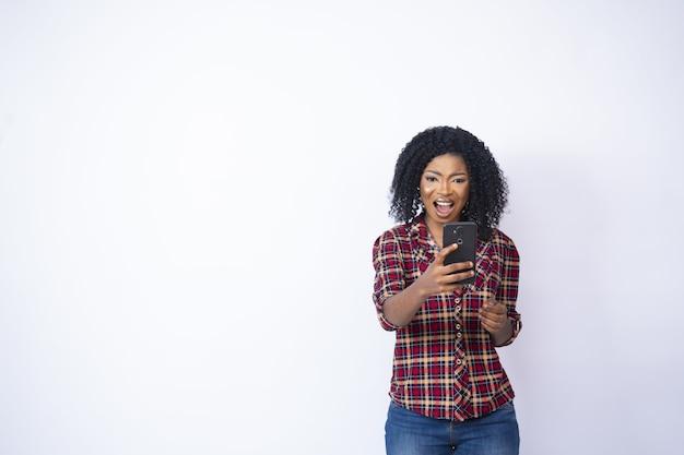 Jonge zwarte vrouw die geschokt en bezorgd naar haar telefoon kijkt