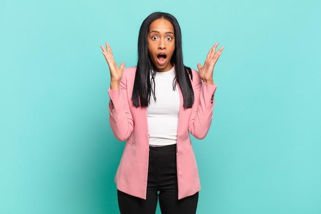 Jonge zwarte vrouw die geschokt en verbaasd kijkt