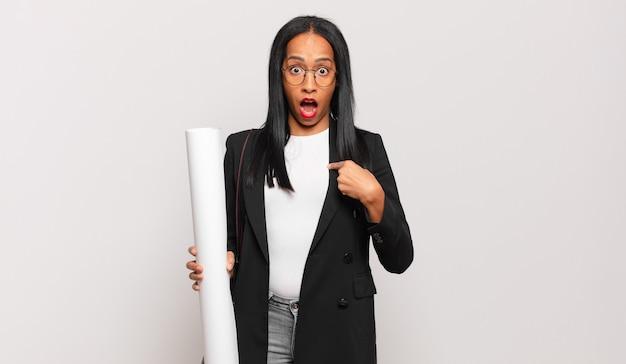Jonge zwarte vrouw die geschokt en verrast kijkt met wijd open mond, wijzend naar zichzelf. architect concept