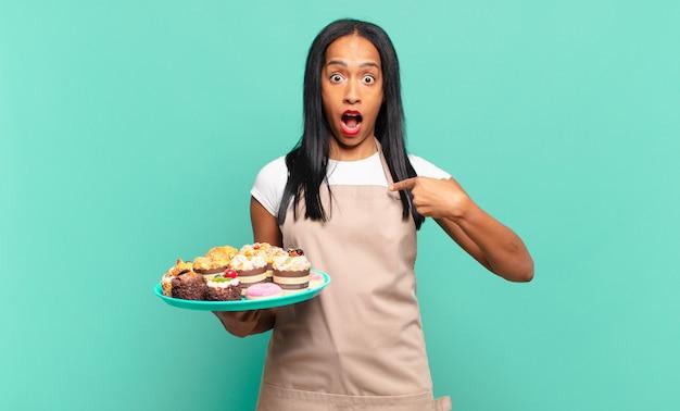Jonge zwarte vrouw die geschokt en verrast kijkt met wijd open mond, wijzend naar zichzelf. bakkerij chef-kok concept