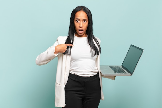 Jonge zwarte vrouw die geschokt en verrast kijkt met wijd open mond, wijzend naar zichzelf. laptopconcept