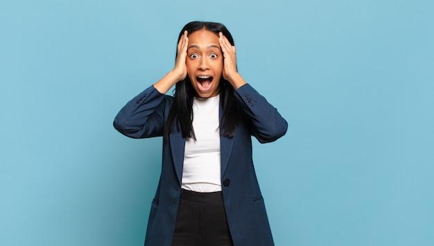 Jonge zwarte vrouw die handen tegen het hoofd steekt, met open mond, zich buitengewoon gelukkig, verrast, opgewonden en gelukkig voelt. bedrijfsconcept