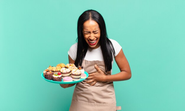 Jonge zwarte vrouw die hardop lacht om een of andere hilarische grap, zich gelukkig en opgewekt voelt, plezier heeft. bakkerij chef-kok concept