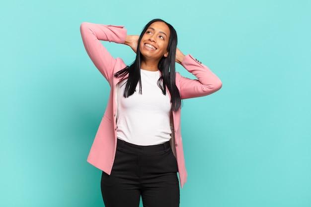 Jonge zwarte vrouw die lacht en zich ontspannen, tevreden en zorgeloos voelt, positief lacht en chillt.