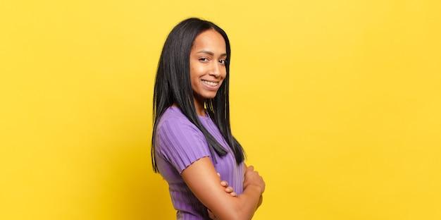 Jonge zwarte vrouw die lacht naar de camera met gekruiste armen en een happy