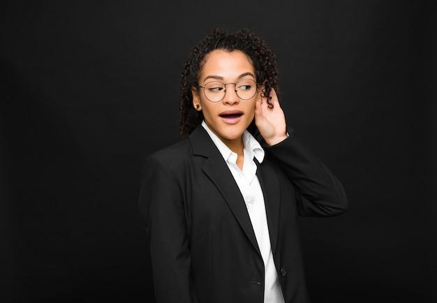 Jonge zwarte vrouw die lacht, nieuwsgierig naar de zijkant kijkt, probeert te luisteren naar roddels of een geheim afluistert tegen een zwarte muur