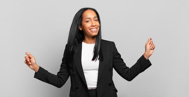Jonge zwarte vrouw die lacht, zich onbezorgd, ontspannen en gelukkig voelt, danst en naar muziek luistert, plezier heeft op een feestje. bedrijfsconcept
