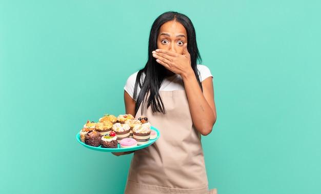 Jonge zwarte vrouw die mond bedekt met handen met een geschokte, verbaasde uitdrukking, een geheim bewaren of oeps zeggen. bakkerij chef-kok concept