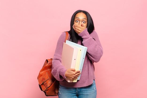 Jonge zwarte vrouw die mond bedekt met handen met een geschokte, verbaasde uitdrukking, een geheim houdt of oeps zegt. studentenconcept