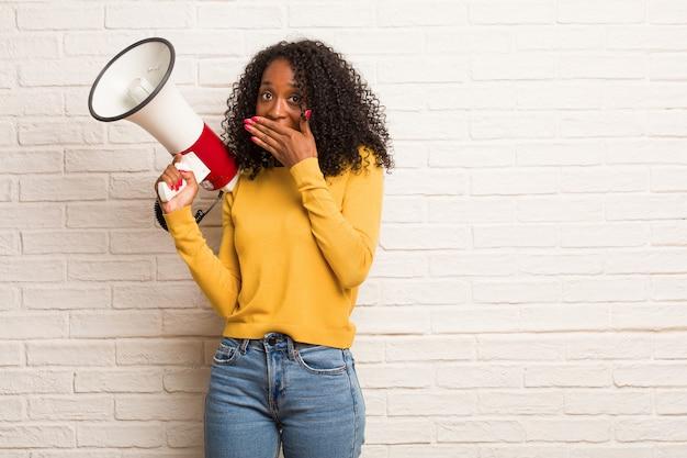Jonge zwarte vrouw die mond, symbool van stilte en onderdrukking, probeert om niets te zeggen