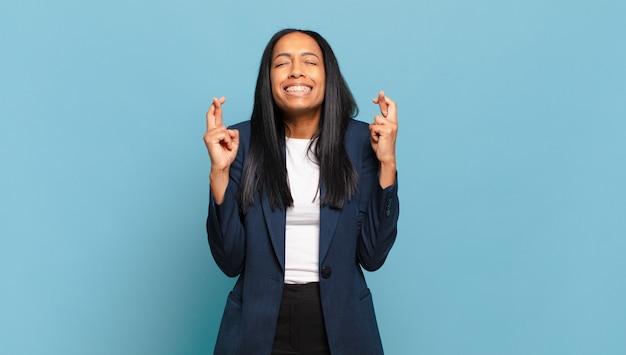 Jonge zwarte vrouw die nerveus en hoopvol is, vingers kruist, bidt en hoopt op geluk. bedrijfsconcept