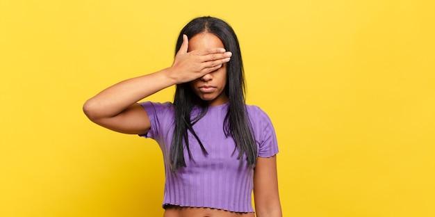 Jonge zwarte vrouw die ogen bedekt met één hand die bang of angstig is, zich afvraagt of blindelings wacht op een verrassing
