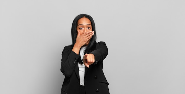 Jonge zwarte vrouw die om je lacht, naar de camera wijst en je voor de gek houdt of bespot. bedrijfsconcept