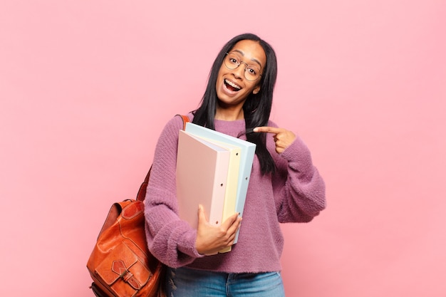 Jonge zwarte vrouw die opgewonden en verrast kijkt en naar de zijkant en naar boven wijst om ruimte te kopiëren. studentenconcept