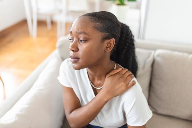 Jonge zwarte vrouw die pijn in de nek voelt, verdrietig op het huisbed. vermoeide vrouw die lijdt aan het kantoorsyndroom vanwege lange uren computerwerk. mooi meisje dat haar gespannen nekspieren masseert