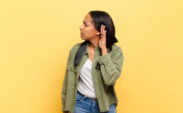 Jonge zwarte vrouw die serieus en nieuwsgierig kijkt, luistert, probeert een geheim gesprek of roddel te horen, afluisteren