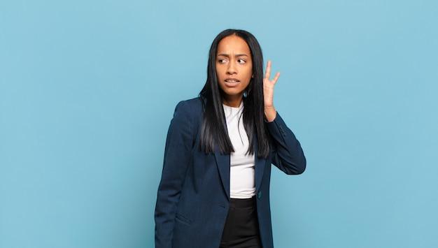 Jonge zwarte vrouw die serieus en nieuwsgierig kijkt, luistert, probeert een geheim gesprek of roddels te horen, afluisteren. bedrijfsconcept
