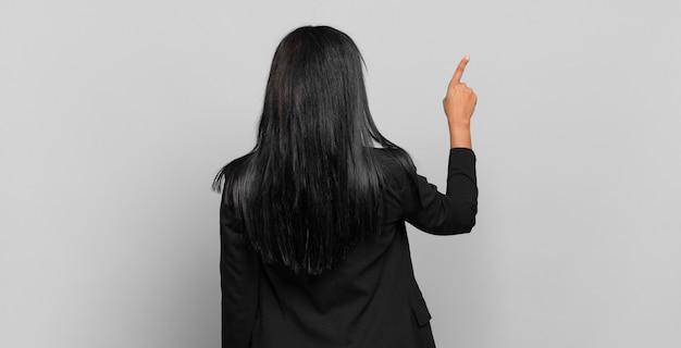 Jonge zwarte vrouw die staat en wijst naar object op kopieerruimte, achteraanzicht. bedrijfsconcept