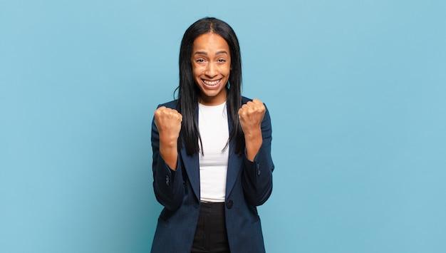 Jonge zwarte vrouw die triomfantelijk schreeuwt, lacht en zich gelukkig en opgewonden voelt terwijl ze succes viert. bedrijfsconcept