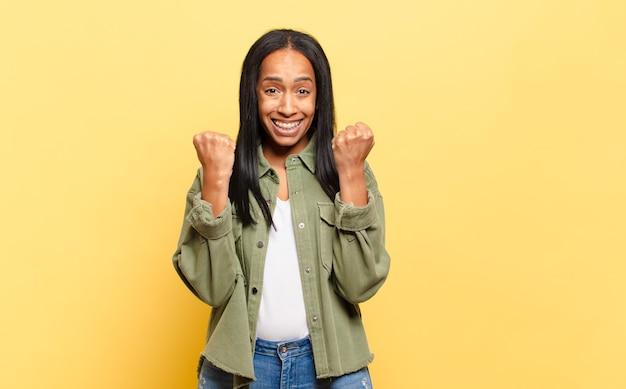 Jonge zwarte vrouw die triomfantelijk schreeuwt, lacht en zich gelukkig en opgewonden voelt terwijl ze succes viert