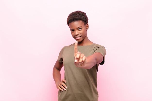 Jonge zwarte vrouw die trots en zelfverzekerd glimlacht en nummer één triomfantelijk laat poseren, zich als een leider op een roze muur voelt