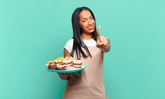 Jonge zwarte vrouw die trots en zelfverzekerd glimlacht en nummer één triomfantelijk poseert