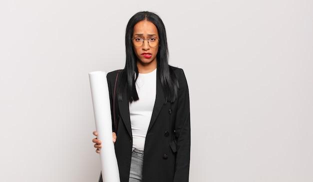 Jonge zwarte vrouw die verbaasd en verward kijkt, lip bijt met een nerveus gebaar, niet wetend het antwoord op het probleem. architect concept