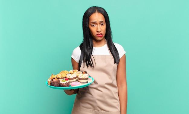 Jonge zwarte vrouw die verbaasd en verward kijkt, lip bijt met een nerveus gebaar, niet wetend het antwoord op het probleem. bakkerij chef-kok concept